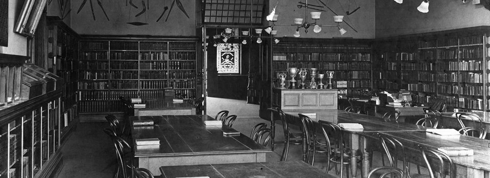 Historical image depicting the interior of Alumni Hall Library in Victoria College, circa 1890s.